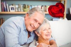 L'immagine composita delle coppie senior ed il cuore rosso balloon 3d Fotografia Stock