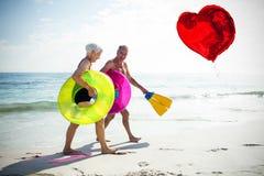 L'immagine composita delle coppie senior sulla spiaggia ed il cuore rosso balloon 3d Immagine Stock