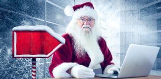 L'immagine composita di Santa paga con la carta di credito su un computer portatile Fotografie Stock