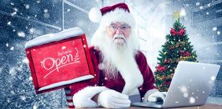 L'immagine composita di Santa paga con la carta di credito su un computer portatile Immagine Stock