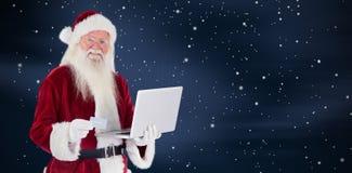 L'immagine composita di Santa paga con la carta di credito su un computer portatile Fotografia Stock