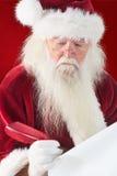L'immagine composita di Santa scrive qualcosa con una piuma Immagine Stock
