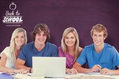 L'immagine composita di un gruppo di studenti con un computer portatile esamina la macchina fotografica Fotografia Stock Libera da Diritti
