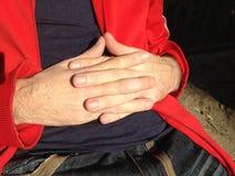 L'immagine del equipaggia le mani afferrate insieme sul suo stomaco Fotografie Stock