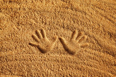 L'immagine del primo piano della mano stampa sul fondo strutturato giallo della sabbia Fotografia Stock