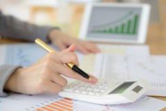 L'immagine della mano della donna con il calcolatore e le carte Fotografie Stock