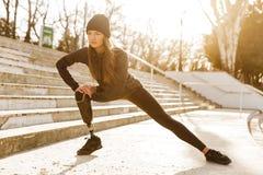 L'immagine della ragazza atletica disabile in abiti sportivi, facente si siede aumenta e fotografia stock libera da diritti