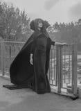 L'immagine della ragazza graziosa di Halloween in un vestito ed in una maschera che cammina attraverso il ponte in bianco e nero immagine stock libera da diritti