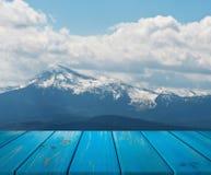 L'immagine della tavola di legno davanti all'estratto ha offuscato il fondo della montagna possono essere usati per esposizione o immagine stock libera da diritti