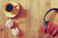 L'immagine delle cuffie sopra la tavola di legno e svuota la carta sgualcita Vista superiore retro filtro Fotografie Stock