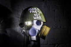 L'immagine di arte di una maschera antigas militare su un muro di mattoni bianco con le ombre con il flash con l'iscrizione fa la immagine stock