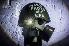L'immagine di arte di una maschera antigas militare su un muro di mattoni bianco con le ombre con il flash con l'iscrizione fa la fotografie stock libere da diritti