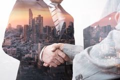 L'immagine di doppia esposizione del handshake dell'uomo d'affari con altro durante la sovrapposizione di alba con l'immagine di  immagini stock libere da diritti