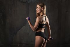 L'immagine di giovane atleta femminile muscolare che indossa l'usura nera di sport sta con la sua di nuovo alla macchina fotograf fotografia stock libera da diritti