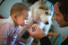 L'immagine di giovane papà alimenta la piccola figlia sveglia con fotografia stock libera da diritti
