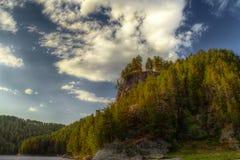 L'immagine di HDR delle rocce con l'abetaia ed il cielo blu Immagini Stock