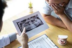 L'immagine di medico o il dentista che presenta con la lastra radioscopica del dente raccomanda paziente nel trattamento di denta immagine stock libera da diritti