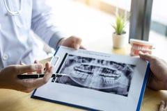 L'immagine di medico o il dentista che presenta con la lastra radioscopica del dente raccomanda paziente nel trattamento di denta immagini stock libere da diritti