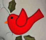 L'immagine di un uccello rosso ha cucito su un tessuto Fotografie Stock Libere da Diritti
