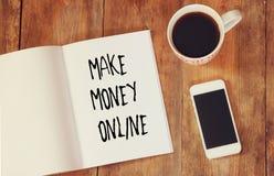 L'immagine di vista superiore del taccuino aperto con la frase rende i soldi online, accanto alla tazza di caffè ed allo smartpho Fotografia Stock