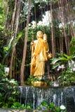 L'immagine dorata di Buddha sta levandosi in piedi in un cespuglio Fotografia Stock