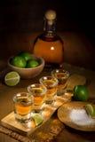 L'immagine verticale di un servizio dei colpi di tequila dell'oro sparsi fuori e aspetta per bere ad un partito Fotografia Stock