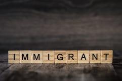 L'immigré de mot est fait de cubes en bois lumineux avec le lette noir images libres de droits