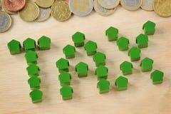 L'impôt de mot écrit avec les maisons miniatures et les euro pièces de monnaie - appui vertical Images stock