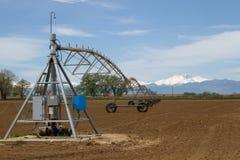 L'impianto di irrigazione del perno in un campo di azienda agricola con desidera supporto di punta Fotografie Stock Libere da Diritti