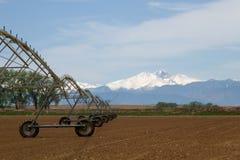 L'impianto di irrigazione del perno in un campo di azienda agricola con desidera supporto di punta Fotografie Stock