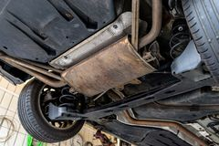 L'impianto di scarico nell'automobile veduta da sotto, l'automobile è sull'ascensore nell'officina dell'automobile immagini stock libere da diritti
