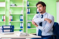 L'impiegato che fa gli esercizi durante la pausa sul lavoro Fotografie Stock Libere da Diritti