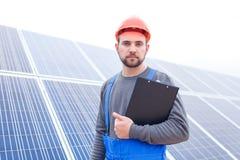 L'impiegato continua premere la compressa contro di lui contro lo sfondo dei pannelli solari Fotografia Stock Libera da Diritti