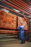 L'impiegato corregge la lavanderia che appende nel locale essiccatoio, le coperte Immagini Stock Libere da Diritti