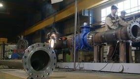 L'impiegato dell'officina salda la costruzione del tubo nella compagnia petrolifera stock footage