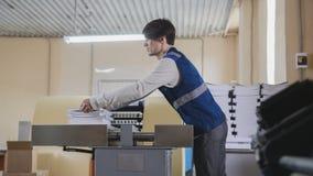 L'impiegato della stamperia sta lavorando alla stampa alla macchina Fotografia Stock Libera da Diritti