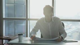 L'impiegato di concetto entra in ufficio, si siede in sedia, guardante i documenti archivi video