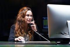L'impiegato di concetto lavora alla tastiera Un impiegato di concetto della donna che si siede allo scrittorio e che lavora con u immagini stock