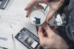 L'impiegato di servizio dei telefoni cellulari tiene una lente d'ingrandimento in sua mano e guarda la mini spina del usb attrave fotografia stock libera da diritti