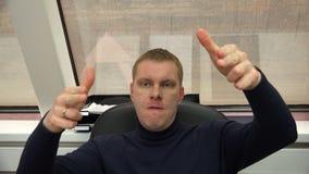 L'impiegato di ufficio in una sedia spara le dita nella macchina fotografica video d archivio