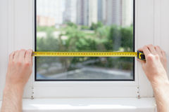 L'impiegato effettua una misura del vetro in una finestra di plastica facendo uso di una misura di nastro Fotografie Stock