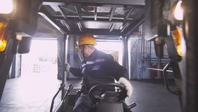 L'impiegato guida il carrello elevatore lungo la roba di passato del deposito archivi video