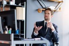 L'impiegato positivo piacevole sta rilassandosi in ufficio Fotografia Stock