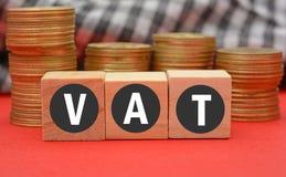 L'imposta sul valore aggiunto sui dadi di legno e sulla valuta conia nel fondo Fotografia Stock Libera da Diritti