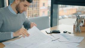 L'imprenditore bello sta lavorando con il nuovo progetto che si siede allo scrittorio in caffè stock footage