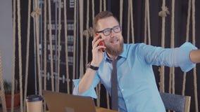 L'imprenditore maschio sta sedendosi nell'ufficio e sta parlando dal telefono cellulare allegramente stock footage