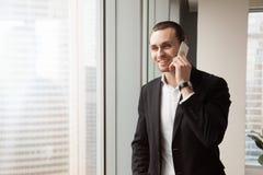 L'imprenditore sorridente risponde alla chiamata in ufficio immagini stock