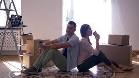 L'inaugurazione di una nuova casa, giovani coppie gode di nuovo appartamento e del tè bevente che si siedono sul pavimento fra le video d archivio