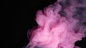 L'inchiostro rosa è caduto in acqua su fondo nero archivi video