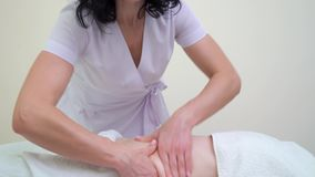 L'inclinaison a tiré du masseur féminin massant l'abdomen de la jeune femme clips vidéos